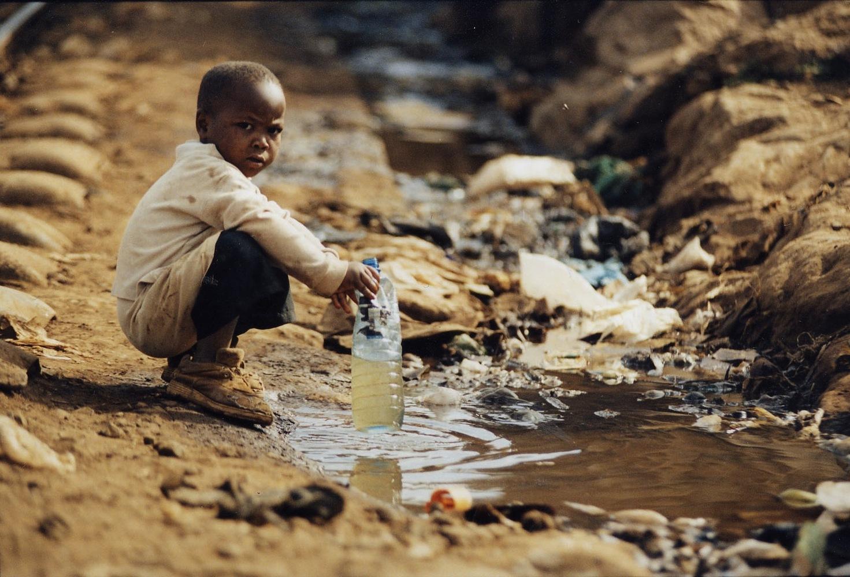кенийский мальчик набирает воду из лужи